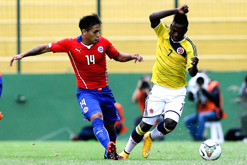 Colombian player Deinner Quinones (R) vies with Chilean player Marcos Bolados during a South American U-20 football match between Colombia and Chile in Maldonado,