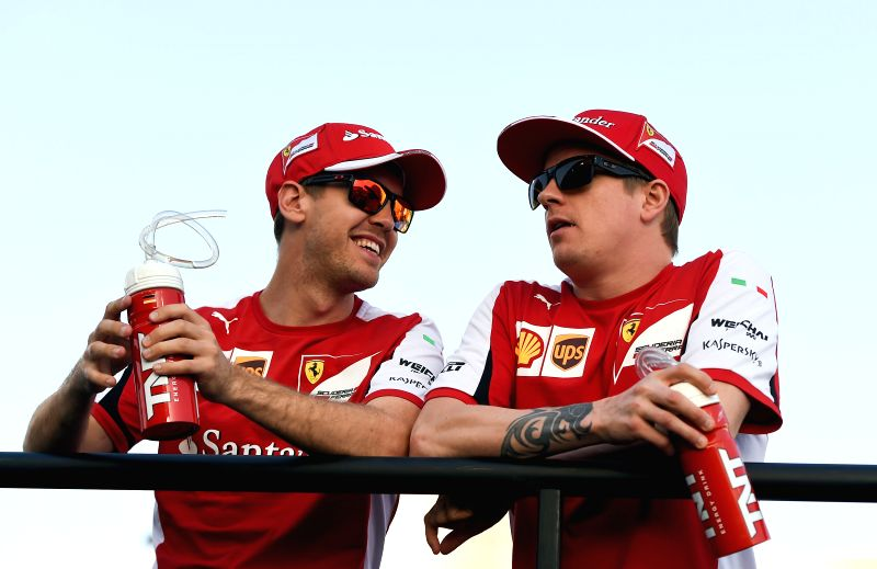 Ferrari drivers Sebastian Vettel of Germany(L), and Kimi Raikkonen of Finland talk to each other during Drivers parade hours before the start of Bahrain's F1 Grand ...