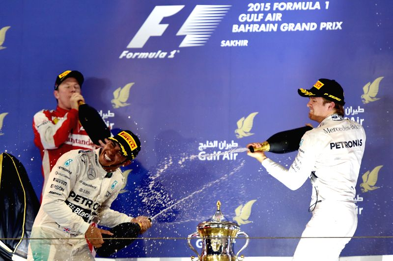 Mercedes Formula One driver Lewis Hamilton (L) of Britain celebrates with his teammate Nico Rosberg on the podium after F1 Grand Prix at Bahrain International ...