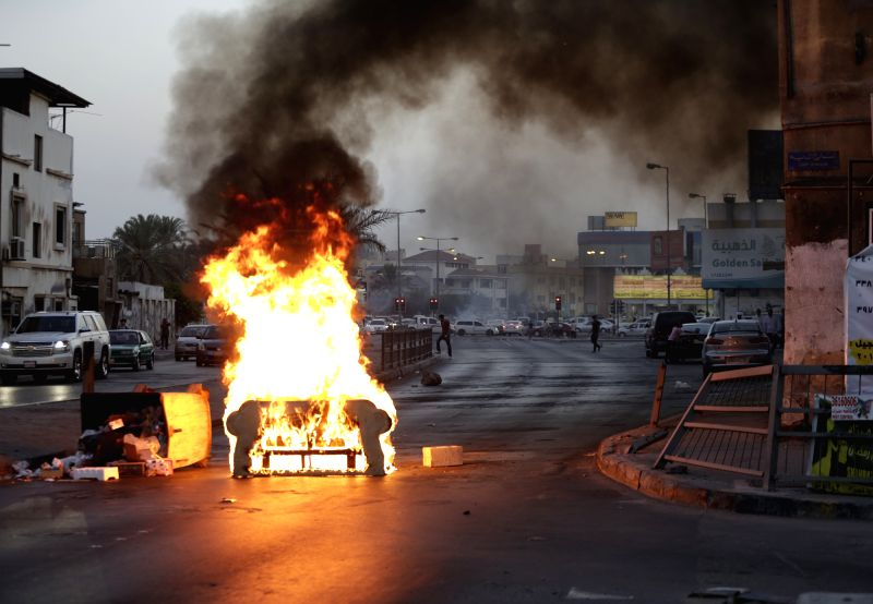 Bahraini Shiite protesters burn an old sofa to block the road during clashes with riot police following an anti-government protest against the manipulation of ...