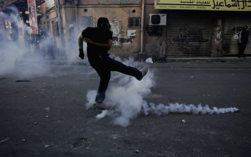 A Bahraini anti-government protester clashes with riot police firing tear gas in Bilad Al Qadeem, Bahrain, on Jan. 2, 2015. Protests swept Friday many parts of ...