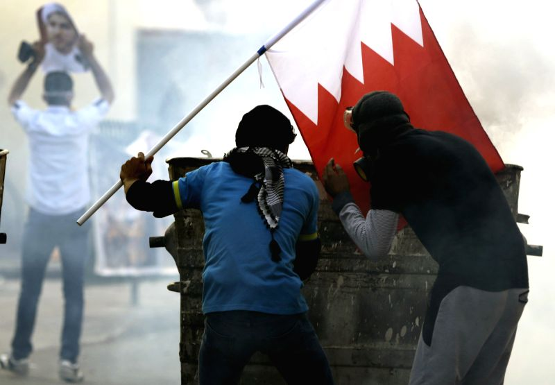 A Bahraini anti-government protester holds a Bahraini national flag during a clash with anti-riot policemen in Bilad Al Qadeem, near Manama, capital of Bahrain, Jan. .
