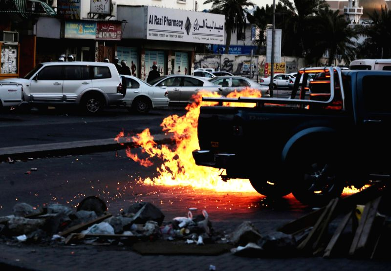 Bahraini anti-government protesters throw a petrol bomb at riot police vehicles during a clash with police in Daih, Bahrain, March 13, 2015. Baharaini shiite ...