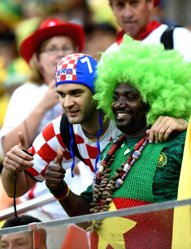 A Croatia's fan (L) and a Cameroon's fan pose for photos before a Group A match between Cameroon and Croatia of 2014 FIFA World Cup at the Arena Amazonia Stadium in .