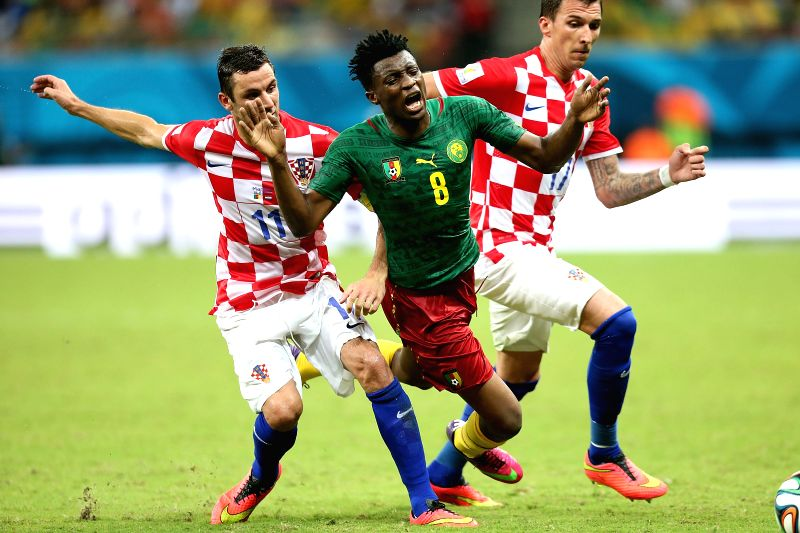 Cameroon's Benjamin Moukandjo (C) falls down during a Group A match between Cameroon and Croatia of 2014 FIFA World Cup at the Arena Amazonia Stadium in Manaus, ...