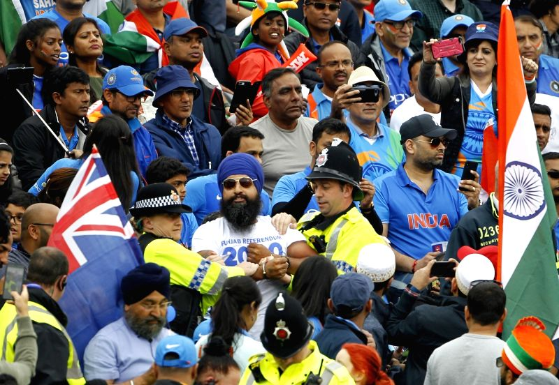 Manchester: A handcuffed Sikh spectator (C) reacts after being taken away by police personnel during the 1st Semi-final match of 2019 World Cup between India and New Zealand at Old Trafford in Manchester, England on July 9, 2019. (Photo: Surjeet Kuma