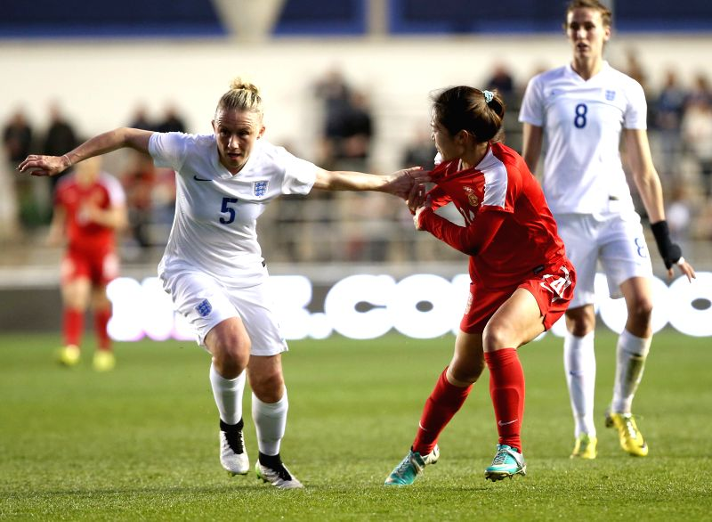 Tang Jiali (R Front) of China is fouled by Laura Bassett of England during the women's international friendly match at the Academy Stadium of Manchester City FC ...