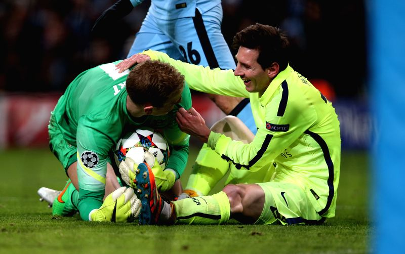 Lionel Messi (R) of Barcelona communicates with Manchester City's goalkeeper Joe Hart after their struggling for the ball during the UEFA Champions league Round ...