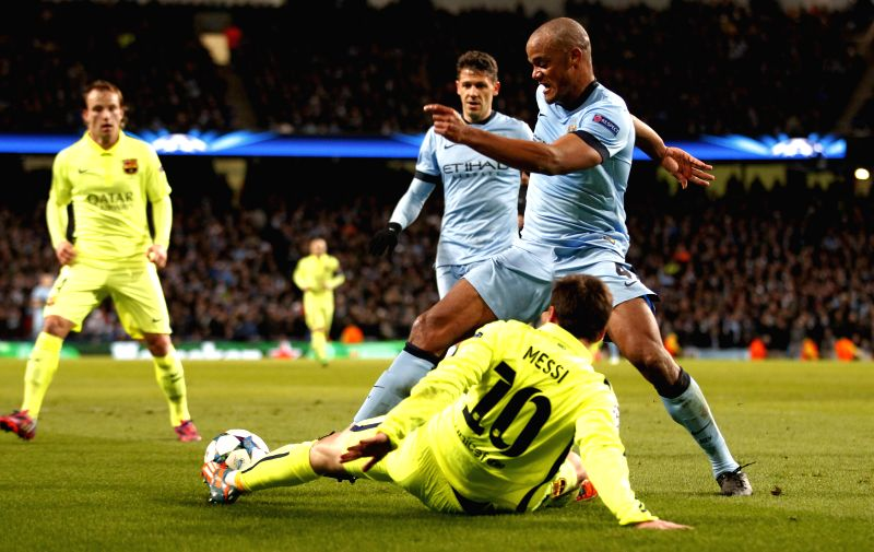 Vincent Kompany (1st R) of Manchester City vies with Lionel Messi (Below) of Barcelona during the UEFA Champions league Round of 16 first leg match between ...