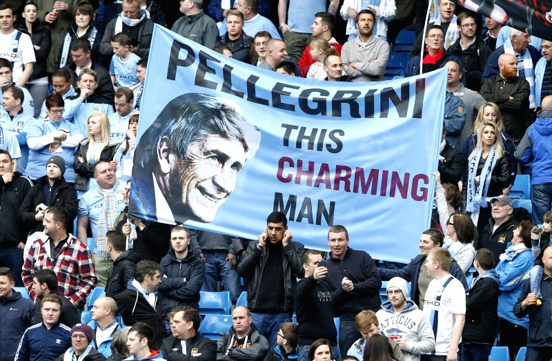 Manchester City fans show off a Manuel Pellegrini banner ahead of the Barclays Premier League match between Manchester City and West Ham United at Etihad Stadium .