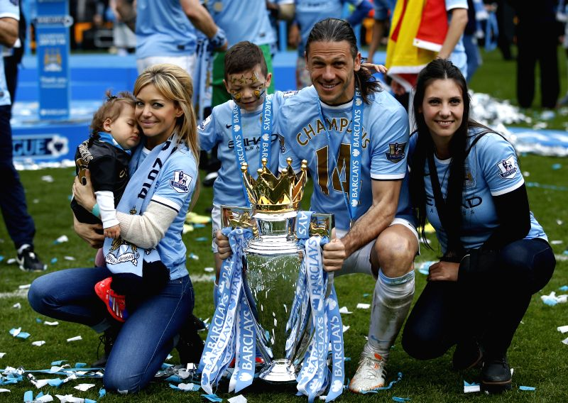 Martin Demichelis (2nd, R) of Manchester City poses with the Premier League trophy and his family at the end of the Barclays Premier League match between ...