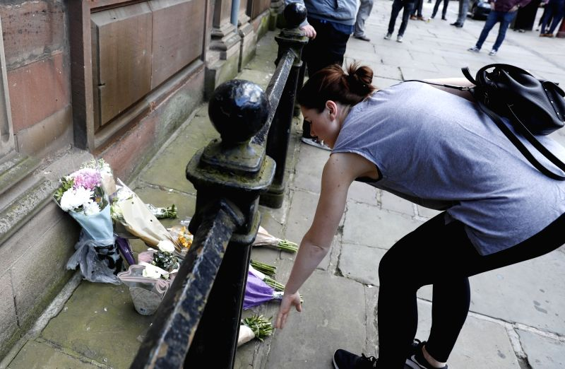 MANCHESTER, May 23, 2017 - A woman lays flowers in memory of the victims of the Manchester Arena bombing in Manchester, Britain, May 23, 2017. A total of 22 people, including children, were killed ...