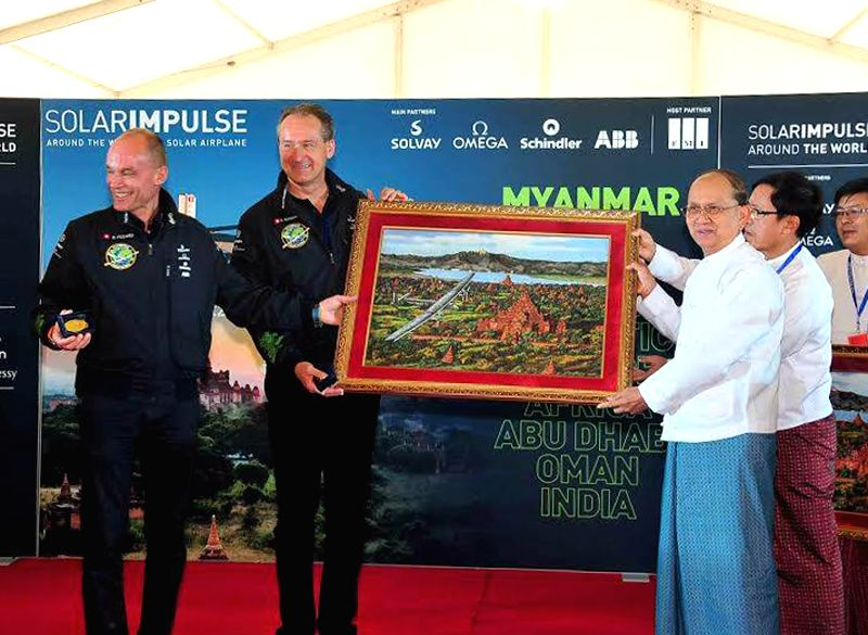 Myanmar President U Thein Sein (R, front) gives a present to Swiss pilots Andre Borschberg (2nd L) and Bertrand Piccard (1st L) during a press conference of the ...