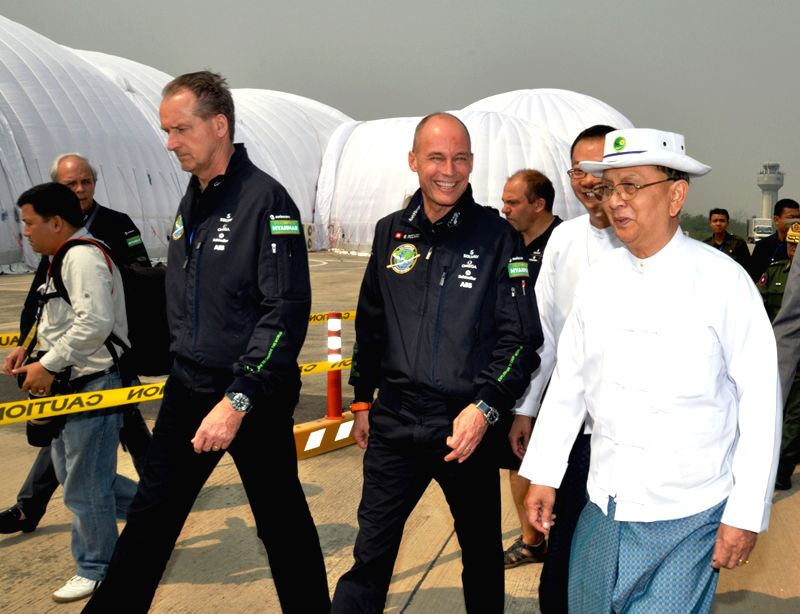 Myanmar President U Thein Sein (R, front) visits the Solar Impulse 2 after its press conference at Mandalay International Airport in Mandalay, Myanmar, March 20, ...