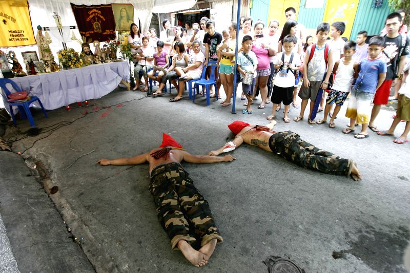 Penitents lie on the ground to pray during a Holy Week ritual to atone for their sins, on a street in Mandaluyong City, the Philippines, April 17, 2014. ..