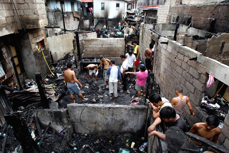 Residents look for reusable materials from their burnt homes after a fire hit a residential area in Mandaluyong City, the Philippines, on July 3, 2014. The .
