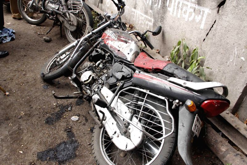 Mangled remains of a motorcycle at the parking lot where an explosive device fixed to a motorcycle blew-up in Pune on July 10, 2014.Three people, including a police constable and a woman, were ...