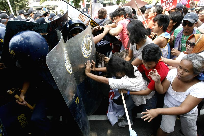 Activists clash with policemen during a protest rally near the U.S. Embassy in Manila, the Philippines, April 23, 2014. The protesters denounce the upcoming state ..