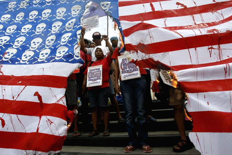 Activists burn a mock U.S. flag during a protest rally in Manila, the Philippines on April 25, 2014. The protesters denounce the upcoming state visit of U.S. ...