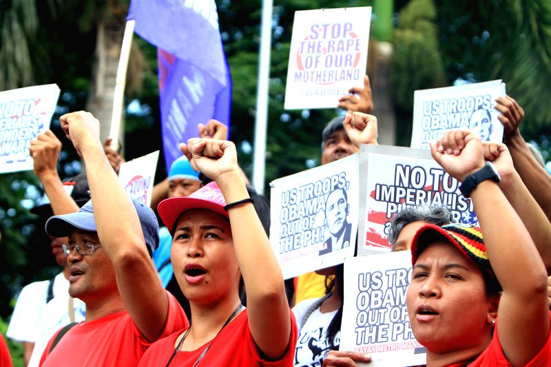 Activists hold placards against the U.S. during a protest rally in Manila, the Philippines on April 25, 2014. The protesters denounce the upcoming state visit of ...