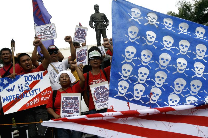 Activists raise their clenched fists behind a mock U.S. flag during a protest rally in Manila, the Philippines on April 25, 2014. The protesters denounce the ...
