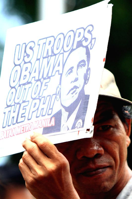 An activist holds a placard against the U.S. during a protest rally in Manila, the Philippines on April 25, 2014. The protesters denounce the upcoming state visit ..