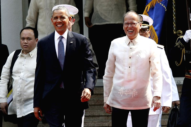 U.S. President Barack Obama (front L) and Philippine President Benigno Aquino III (front R) walk during an arrival ceremony at the presidential palace in Manila, the