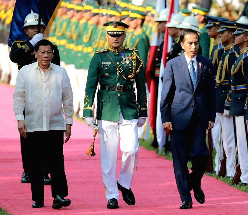 MANILA, April 28, 2017 - Indonesian President Joko Widodo (R, front) and Philippine President Rodrigo Duterte (1st, L) walk in front of honor guard in Manila, the Philippines, April 28, 2017. Widodo ...
