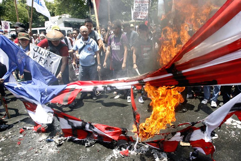 Activists burn a mock U.S. flag during a protest rally near the U.S. Embassy in Manila, the Philippines, April 29, 2014. U.S. President Barack Obama on Tuesday ...