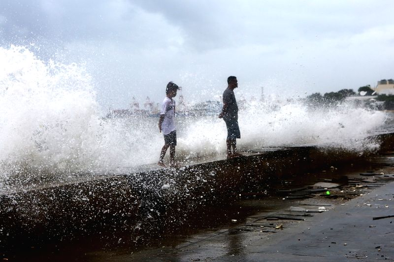 MANILA, Aug. 11, 2018 - A wave crashes on people as they walk along Manila Bay, the Philippines, Aug. 11, 2018. Typhoon Yagi brought gales and heavy rain in parts of Metro Manila.