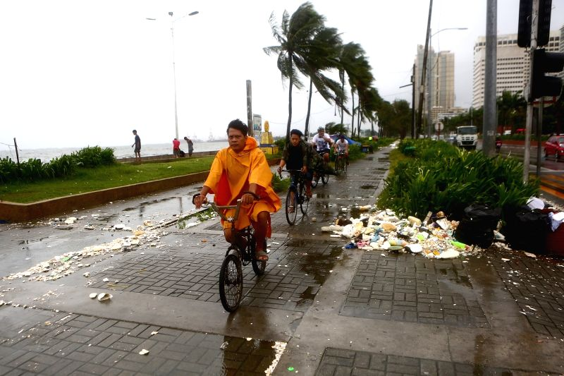 MANILA, Aug. 11, 2018 - People ride their bikes through rain and wind along Manila Bay, the Philippines, Aug. 11, 2018. Typhoon Yagi brought gales and heavy rain in parts of Metro Manila.