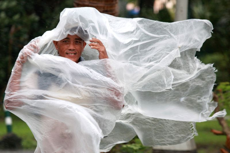 A man uses a plastic sheet to shield himself from the monsoon rains and strong winds from typhoon Halong in Manila, the Philippines, Aug. 5, 2014. Heavy rains brought