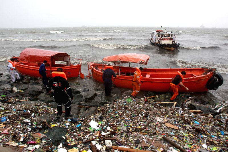 People secure their boats washed ashore by the monsoon rains from typhoon Halong in Manila, the Philippines, Aug. 5, 2014. Heavy rains brought by the monsoon and ...