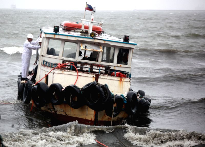 People secure their boat washed ashore by the monsoon rains from typhoon Halong in Manila, the Philippines, Aug. 5, 2014. Heavy rains brought by the monsoon and ...