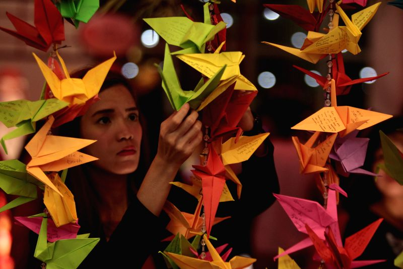 A lady hangs a paper crane with her wishes written on it during the Chinese New Year's Eve celebration at Chinatown in Manila, the Philippines, on Feb. 18, 2015. ...