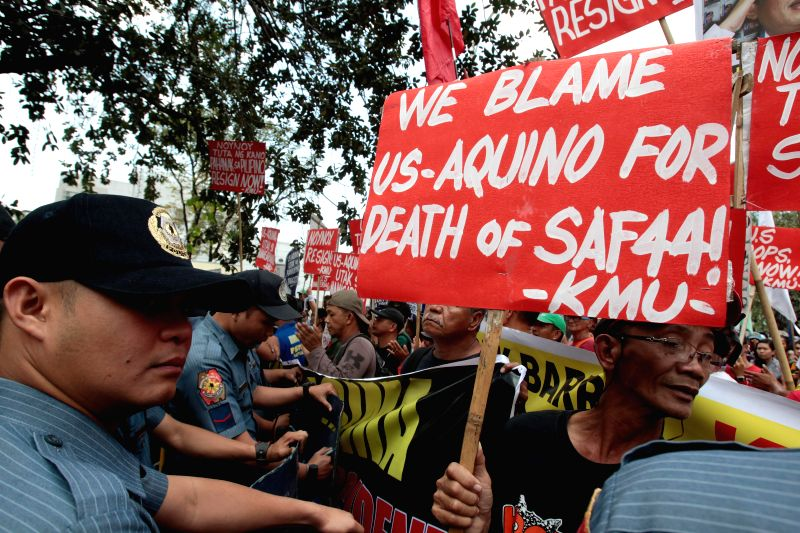 Activists are blocked by policemen during a protest rally near the U.S. Embassy in Manila, the Philippines, Feb. 4, 2015. The activists called for justice for the ...