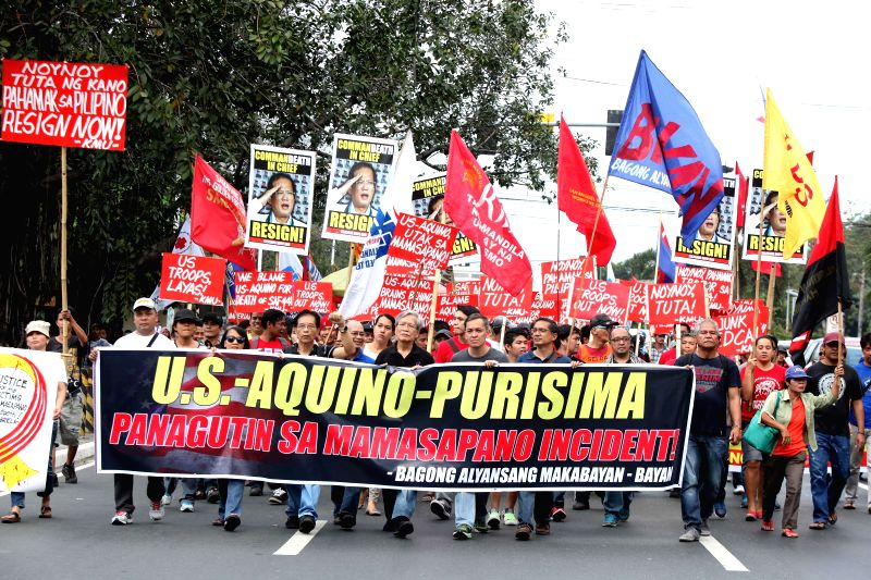 Activists hold placards during a protest rally near the U.S. Embassy in Manila, the Philippines, Feb. 4, 2015. The activists called for justice for the slain members .