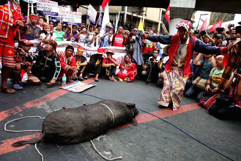Indigenous people perform a ritual against the militarization in their communities during a protest rally near the Malacanan Palace in Manila, the Philippines, Nov. 24, 2014. The protesters ..