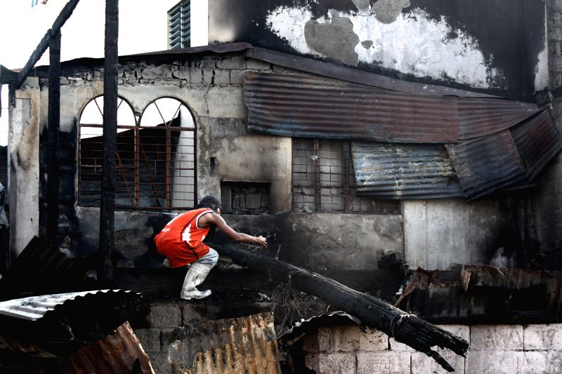 A resident looks for reusable materials after a fire hit a slum area in Manila, the Philippines, Jan. 13, 2015. More than 100 homes were razed in the fire, leaving ..