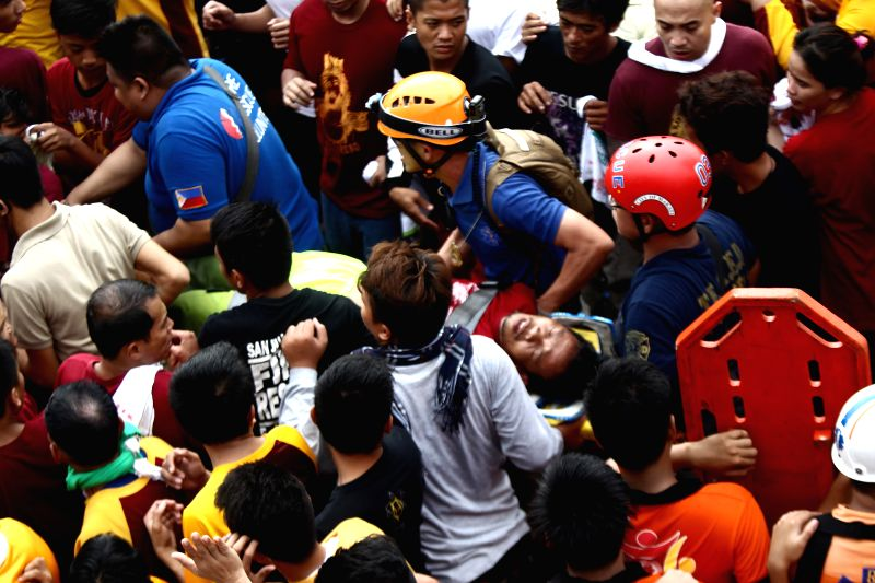 People carry an unconscious fellow devotee after he fainted during the annual feast of the Black Nazarene in Manila, the Philippines, Jan. 9, 2015. One person died ...