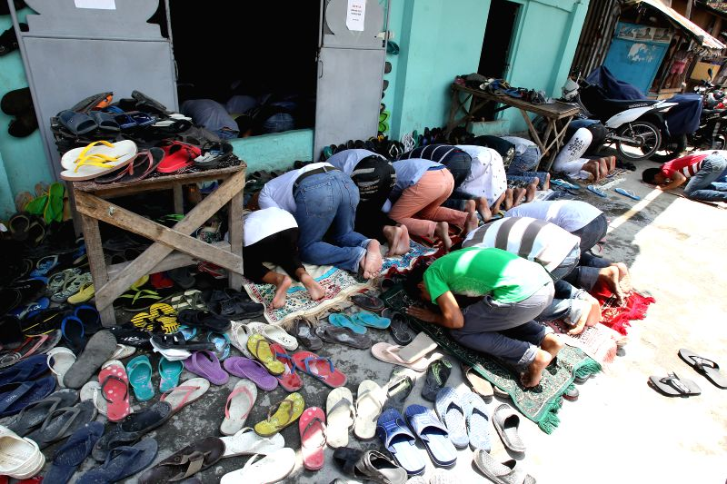 Muslims kneel in prayer outside a mosque in Manila, the Philippines, July 11, 2014. Muslims continue their observance of the Islamic holy month of Ramadan. ...