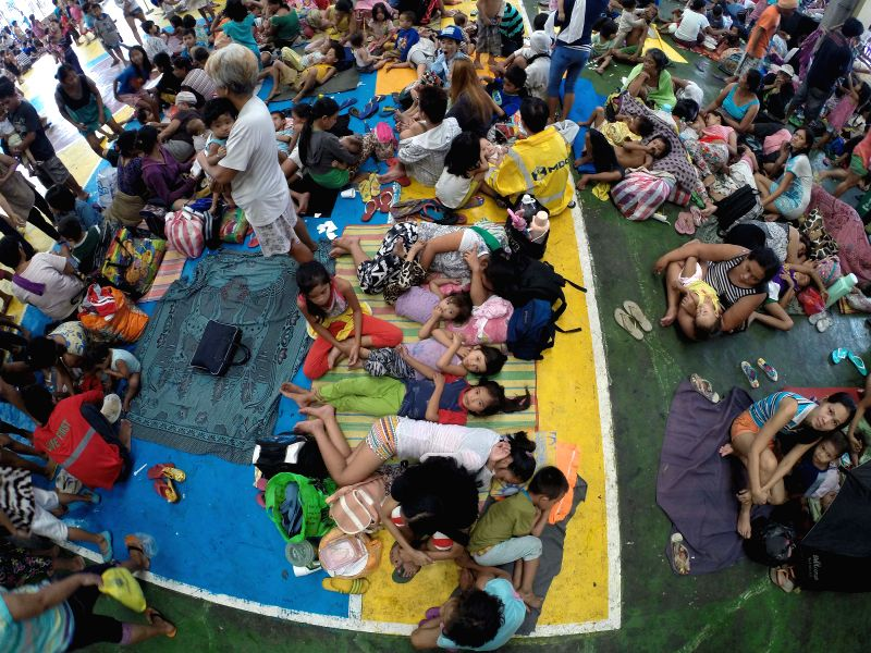 Residents take shelter in a covered court after evacuating from their homes as typhoon Rammasun batters Manila, the Philippines, July 16, 2014. At least 5 people ...