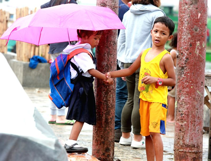 MANILA, July 16, 2018 - A boy assists his sister to school in the rain caused by the tropical depression Henry in Manila, the Philippines, July 16, 2018.