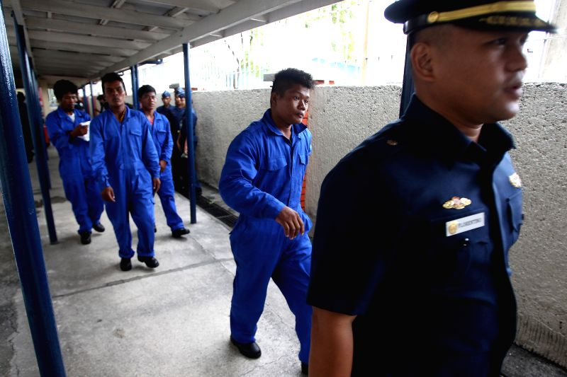 A member of the Philippine Coast Guard (PCG) leads the four rescued Filipino fishermen inside the PCG Headquarters in Manila, the Philippines, on July 17, 2014. The .