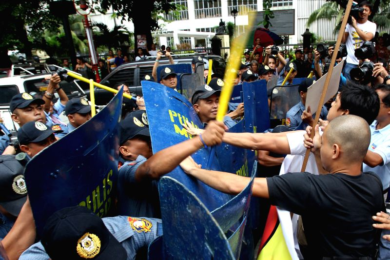 Activists clash with policemen during a protest rally in Manila, the Philippines, July 4, 2014. The activists marked the 68th Philippine-American Friendship Day with .