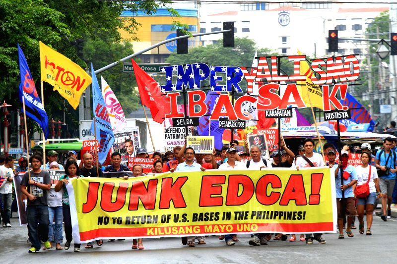 Activists march during a protest rally in Manila, the Philippines, July 4, 2014. The activists marked the 68th Philippine-American Friendship Day with a protest rally