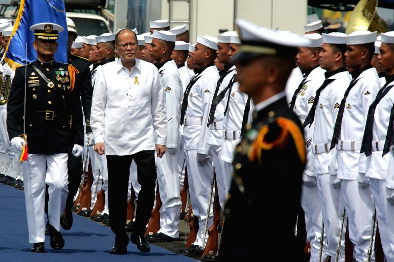 MANILA, June 1, 2016 - Philippine President Benigno Aquino III (2nd L, front) walks in front of members of the Philippine Navy during the commissioning of new naval ships at Pier 13 in Manila, the ...