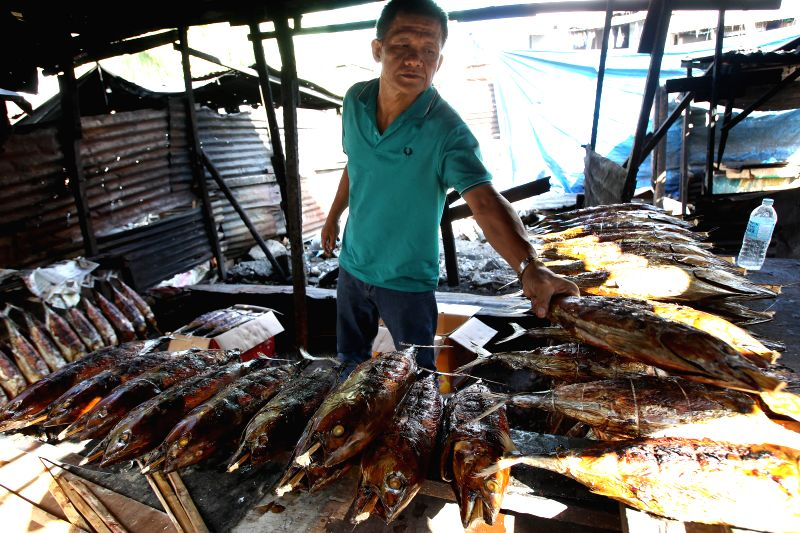 A Muslim man sells smoked tuna at a Muslim community in Manila, the Philippines, June 29, 2014. Muslims around the world are observing the first day of the fasting ..