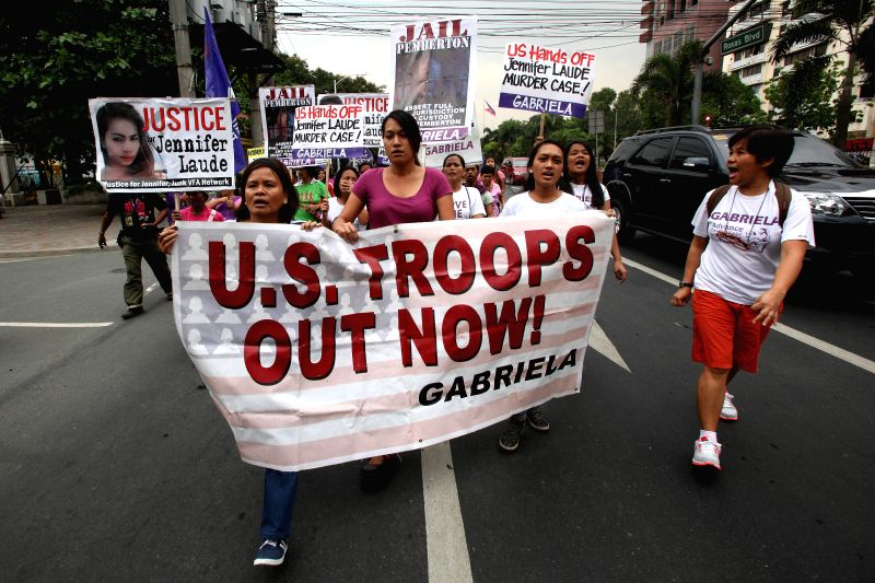 Activists holding a banner and placards shout slogans during a protest rally near the U.S. Embassy in Manila, the Philippines, March 24, 2015. Activists called for ...
