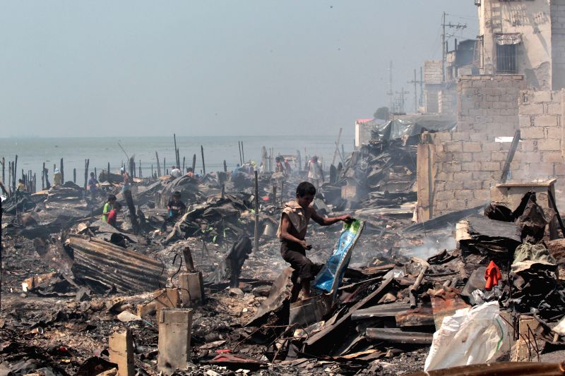 Residents looks for their belongings from their burnt homes after a fire at a slum area in Manila, the Philippines, March 3, 2015. Around 5,000 shanties were razed ...